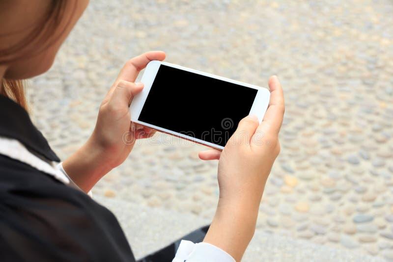 Close-up de uma mão da mulher que guarda o vídeo de observação do telefone celular imagens de stock
