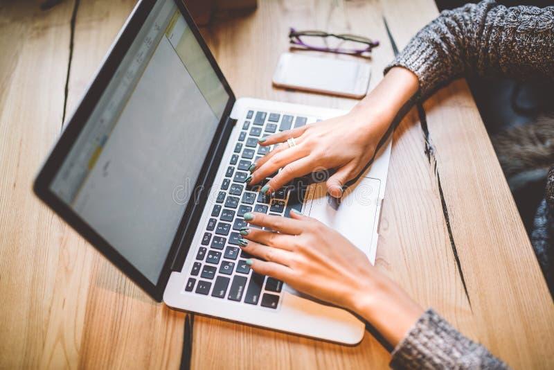 Close-up de uma mão do ` s da moça em uma tecnologia cinzenta do portátil do uso da camiseta em uma tabela de madeira em um café  imagem de stock royalty free