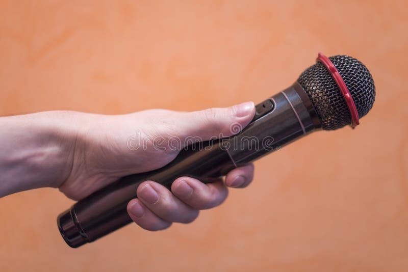 Close-up de uma mão do ` s do homem que guarda um microfone preto em uma laranja fotografia de stock