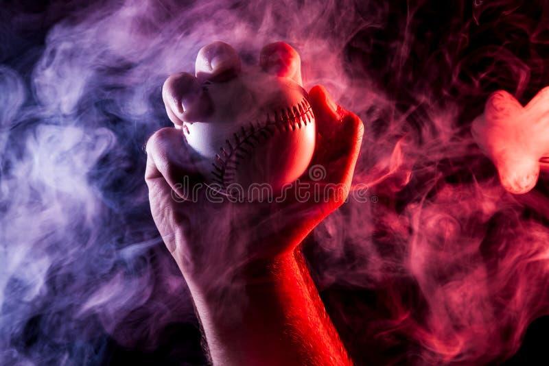 Close-up de uma mão masculina forte que guarda uma bola branca do basebol fotografia de stock