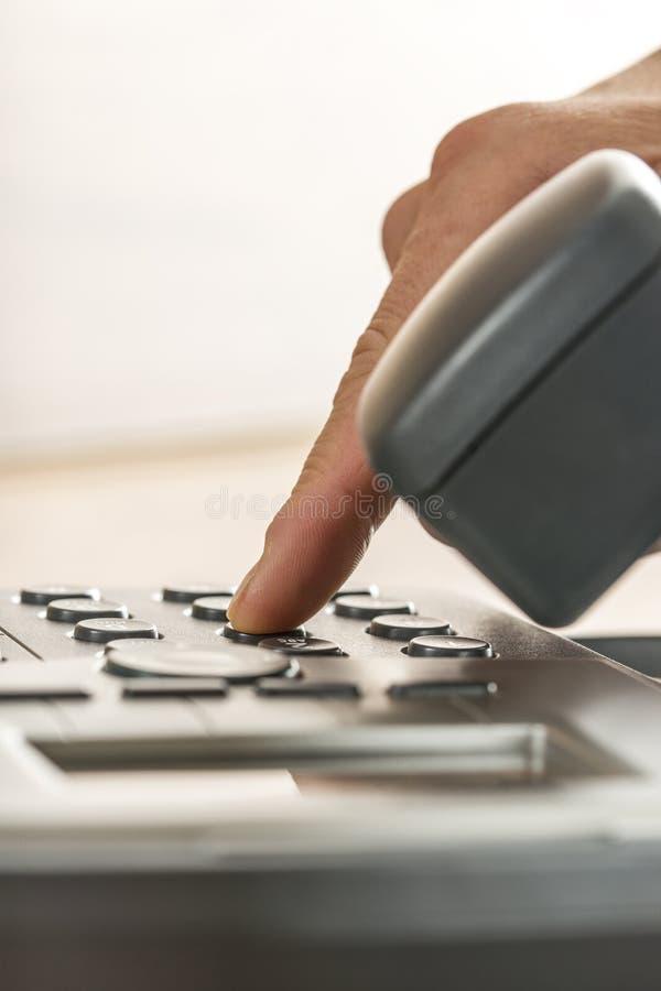 Close up de uma mão masculina que faz um telefonema discando um classica imagens de stock royalty free