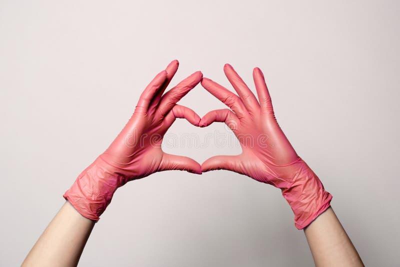Close up de uma mão nas luvas cor-de-rosa médicas de borracha do látex dobradas em um sinal do coração Isolado no fundo branco Pa imagens de stock
