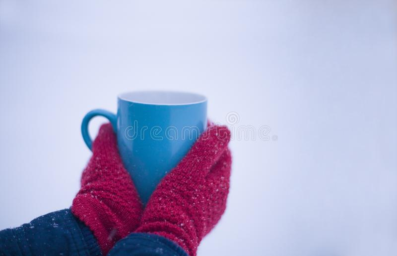 Close-up de uma mão vermelho-gloved que guarda um copo com uma bebida quente no inverno na neve foto de stock