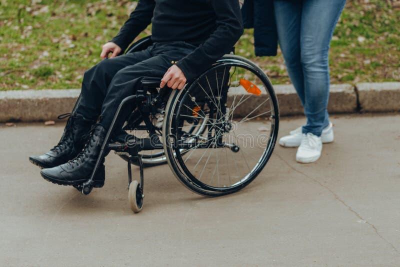Close-up de uma m?o masculina em uma roda de uma cadeira de rodas durante uma caminhada no parque Caminhada junto no parque imagem de stock royalty free