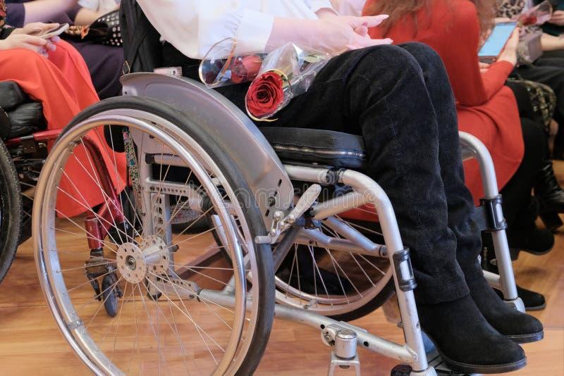 Close-up de uma menina em uma cadeira de rodas que guarda um ramalhete das flores em suas m?os O conceito da prote??o social, igu foto de stock