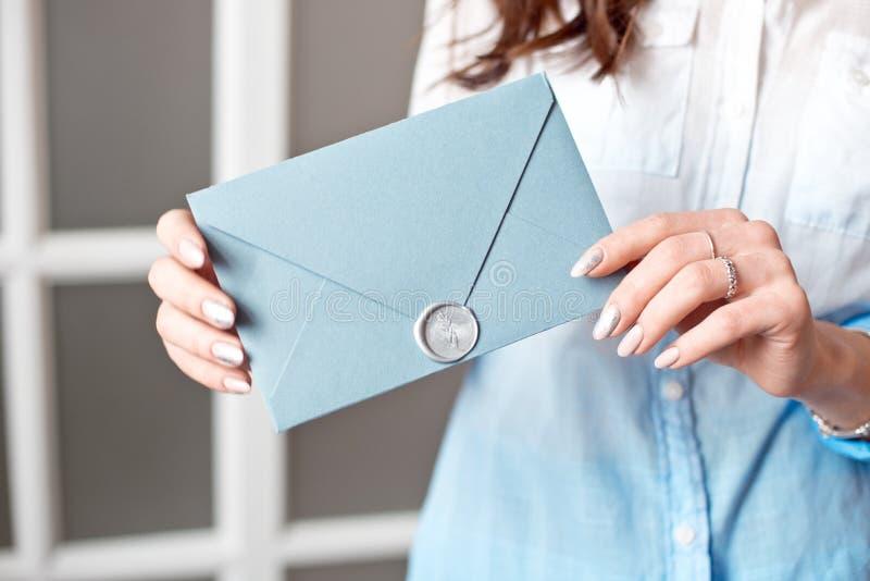 Close-up de uma moça que guarda um envelope retangular azul com convites, cartão do presente do produtos e serviços imagem de stock royalty free