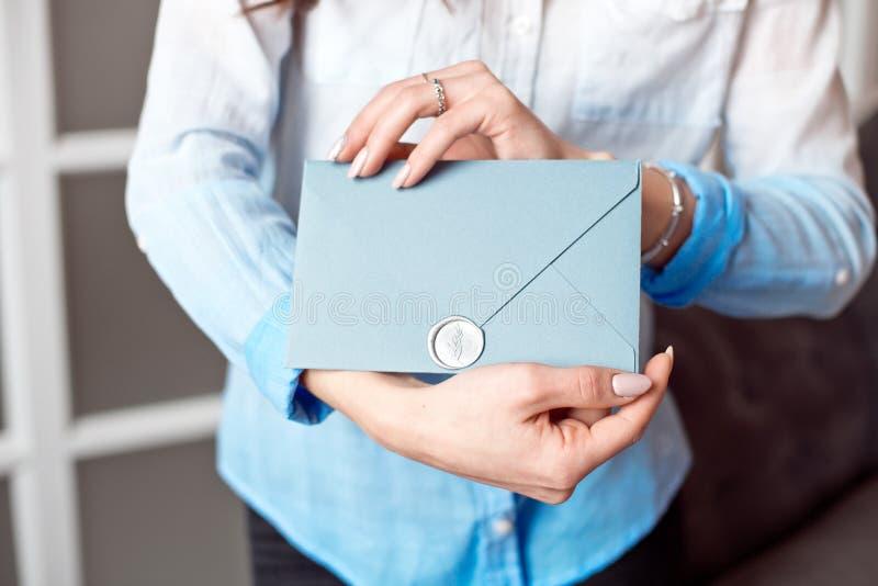 Close-up de uma moça que guarda um envelope retangular azul com convites, cartão do presente do produtos e serviços fotografia de stock royalty free