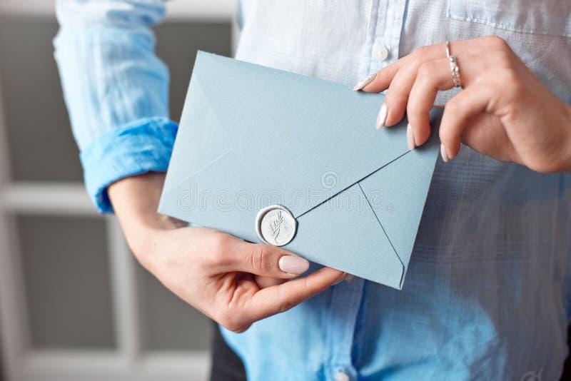 Close-up de uma moça que guarda um envelope retangular azul com convites, cartão do presente do produtos e serviços imagens de stock