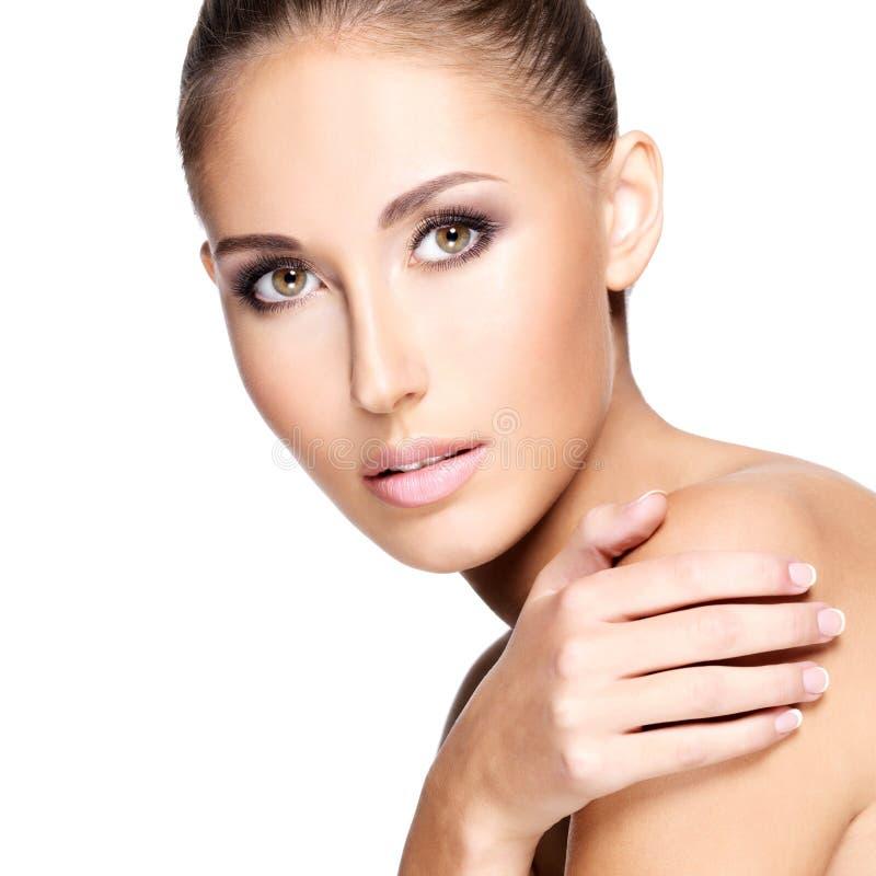 Close up de uma mulher bonita com a pele saudável que toca em seu shou fotografia de stock royalty free