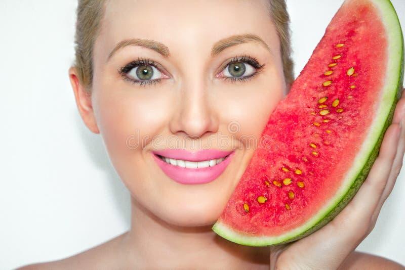 Close-up de uma mulher bonita nova com uma melancia O conceito da pele saudável e hidratada foto de stock royalty free