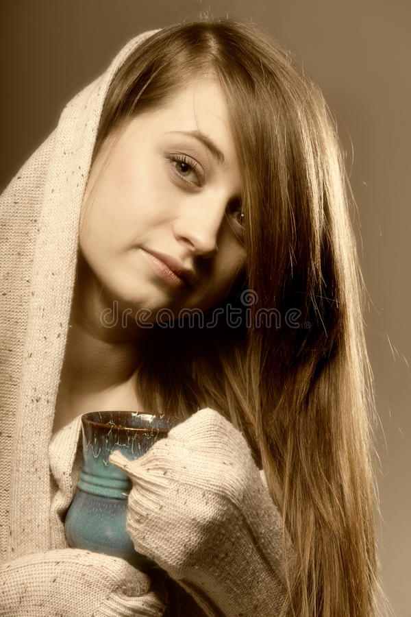Mulher bonita que daydreaming ao guardarar um copo do T foto de stock