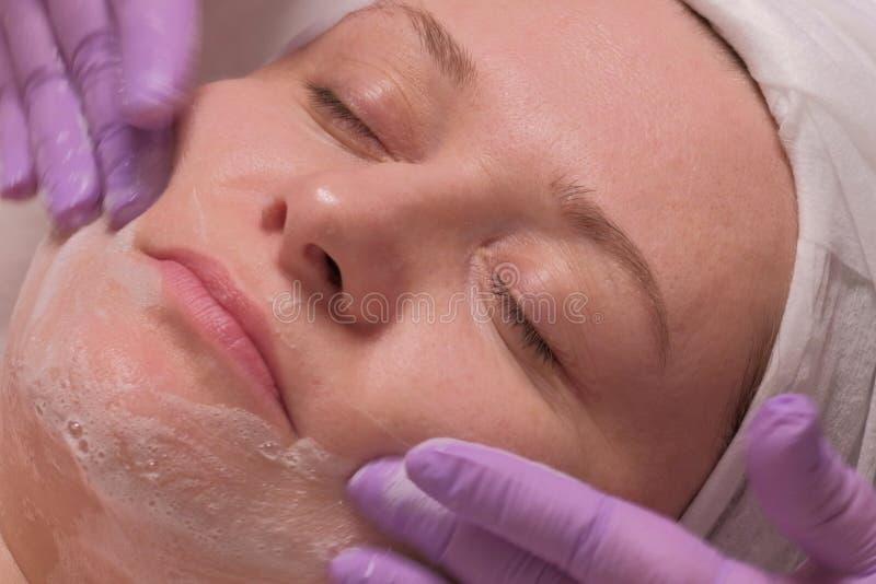 Close-up de uma mulher com olhos fechados em um salão de beleza As mãos de um cosmetologist em luvas lilás lavam a pele de uma mu imagens de stock royalty free