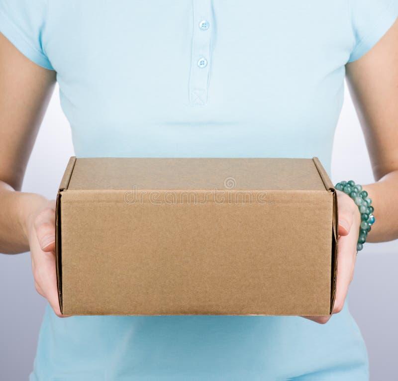 Close up de uma mulher em um polo azul que guarda uma caixa de cartão fotos de stock royalty free