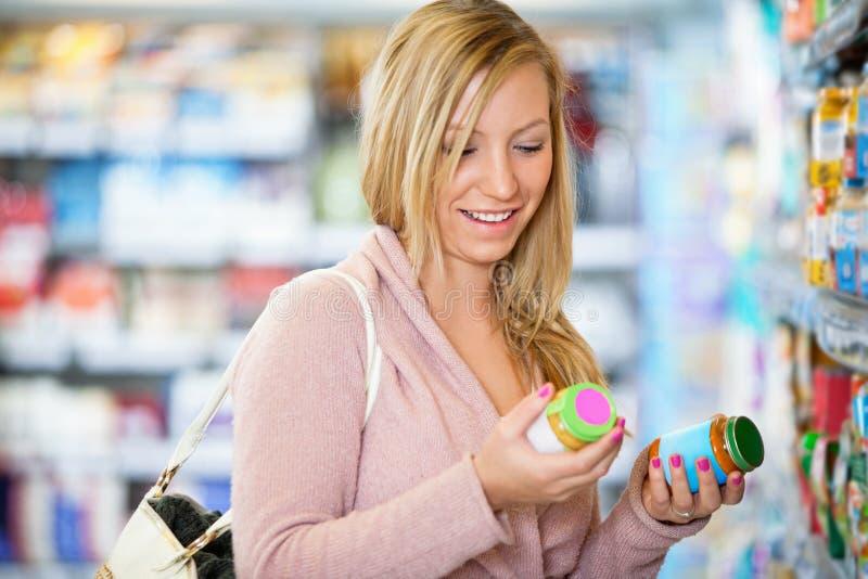 Close up de uma mulher nova que sorri ao prender o frasco imagem de stock
