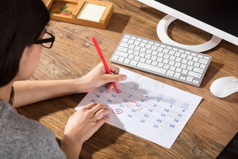 Close-up de uma mulher que circunda a data no calendário imagens de stock