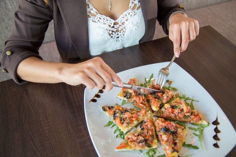 Close up de uma mulher que come o almoço com faca e forquilha foto de stock
