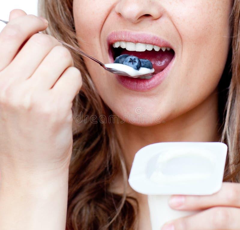 Close-up de uma mulher que come um yogurt imagem de stock royalty free