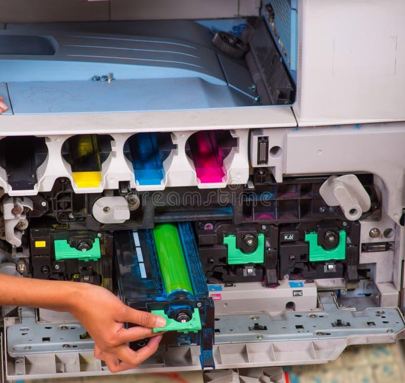 Close up de uma mulher que fixa uma fotocopiadora durante a manutenção, guardando um tonalizador fotografia de stock