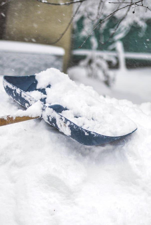 Close-up de uma pá da neve Após uma queda de neve pesada, um homem limpa a jarda das trações da neve imagens de stock royalty free