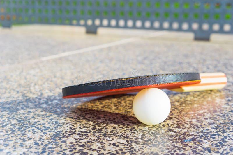 Close-up de uma pá do tênis de mesa com uma bola do branco do tênis de mesa imagens de stock royalty free