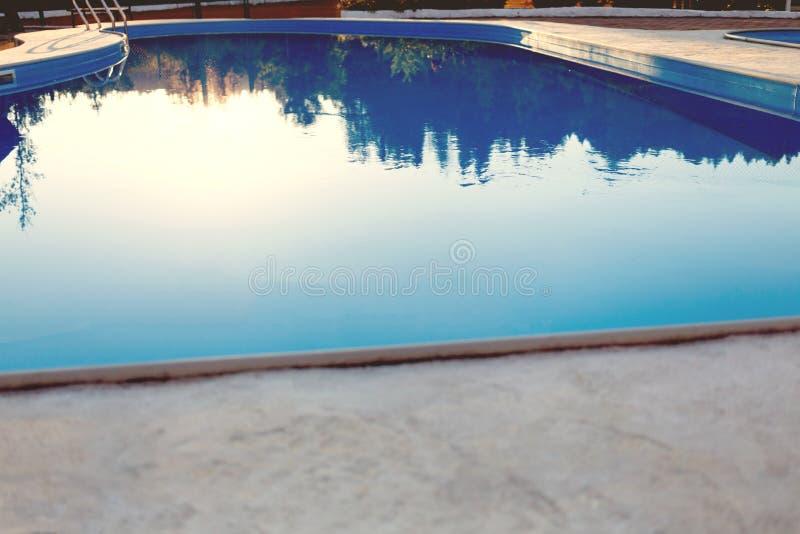 Close-up de uma parte da piscina com uma escada de aço inoxidável e da água azul no por do sol As férias de verão, feriados, rela imagens de stock royalty free