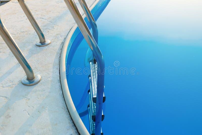 Close-up de uma parte da piscina com uma escada de aço inoxidável e da água azul no por do sol As férias de verão, feriados, rela foto de stock