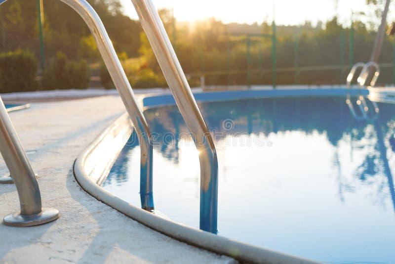 Close-up de uma parte da piscina com uma escada de aço inoxidável e da água azul no por do sol As férias de verão, feriados, rela imagens de stock