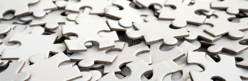 Close-up de uma pilha de elementos uncompleted de um enigma branco Um grande número de partes retangulares de um grande mosaico b fotos de stock
