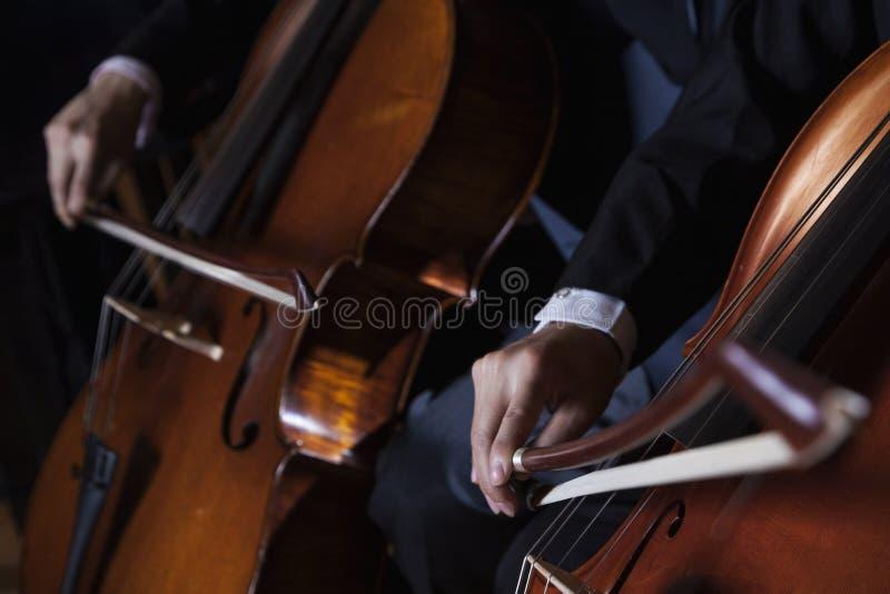 Close-up de uma seção mestra de dois violoncelistas que jogam o violoncelo durante um desempenho fotografia de stock royalty free