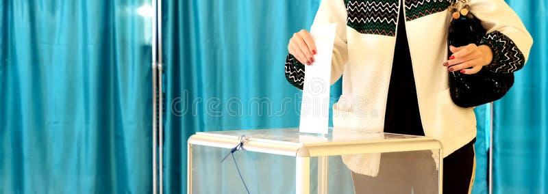 Close-up De vrouwelijke hand zet een stembriefje in een transparant vakje Achtergrond voor een uitnodigingskaart of een gelukwens stock afbeelding