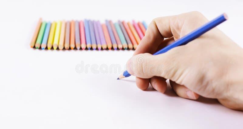 close-up de vrouwen` s hand trekt een blauw potlood op een wit blad van pap stock afbeeldingen
