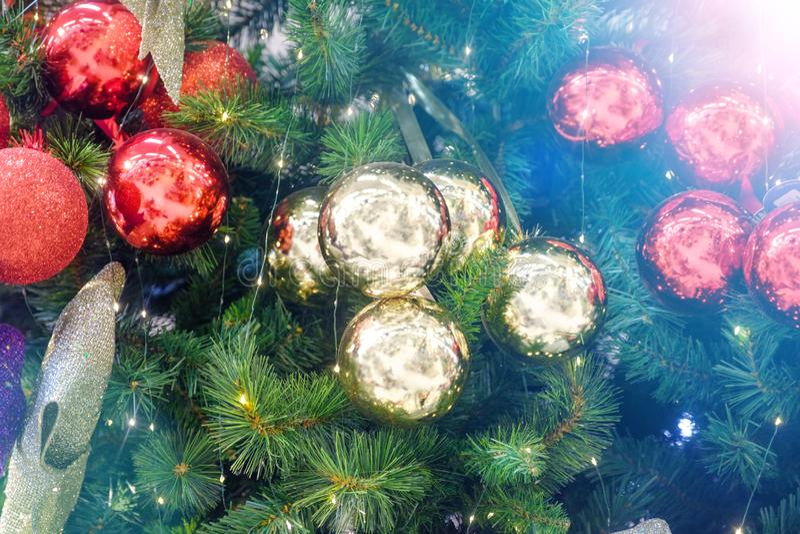 Close up decorado da árvore de Natal Bolas vermelhas e douradas e festão iluminada com lanternas elétricas Macro das quinquilhari fotografia de stock