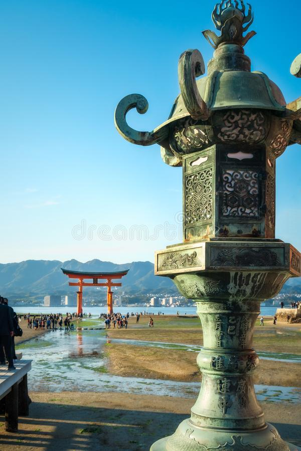 Bronze lantern with the famous Torii Gate in the background, Miyajima Island, Japan. Close-up of a decorated bronze lantern with the famous Torii Gate in soft royalty free stock image