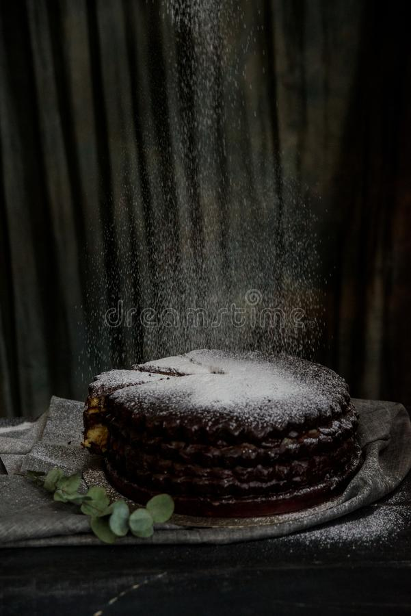 Covering chocolate cake with sugar powder. Close up decorating chocolate cake with sugar powder. Dark vintage stillife royalty free stock photo