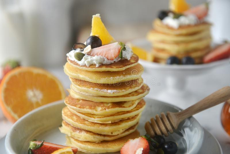 Close-up, Decorating a stack of pancakes by baker hands with blueberries, strawberries, orange and whipping cream. stock image