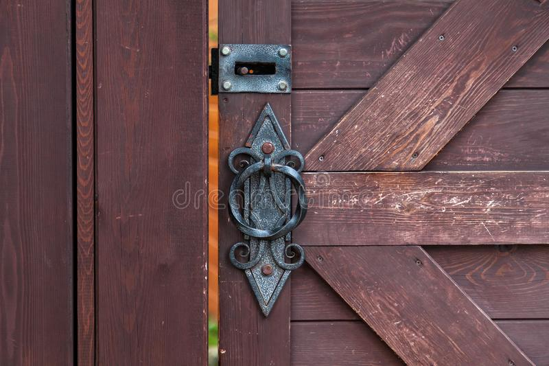 Close-up on a decorative forged Handle and bolt in antique style with a twisted pattern on a brown wooden door. Construction and. Decoration of buildings royalty free stock images