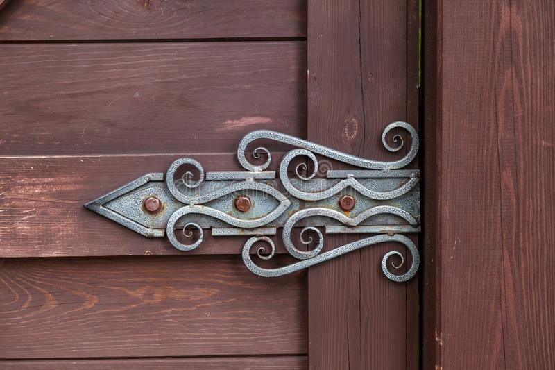 Close-up on a decorative forged hinge in antique style with a twisted pattern on a brown wooden door. Construction and decoration. Of buildings royalty free stock images