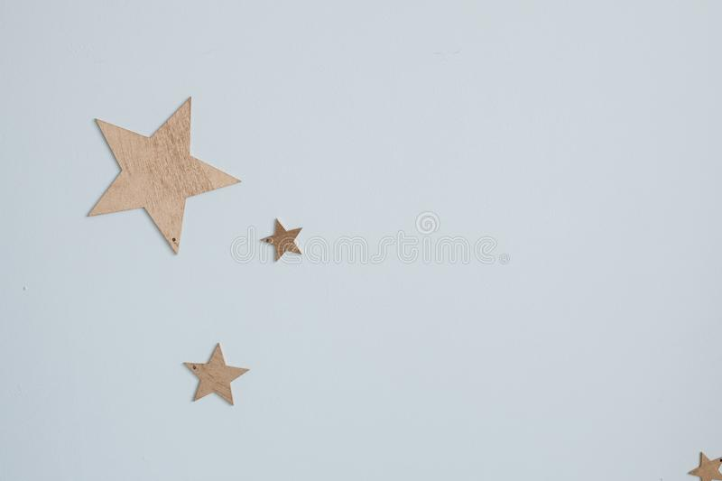 Decorative golden stars on the wall. Close-up of decorative golden paper stars of different size on plain blue wall like. Close-up of decorative golden paper stock photos