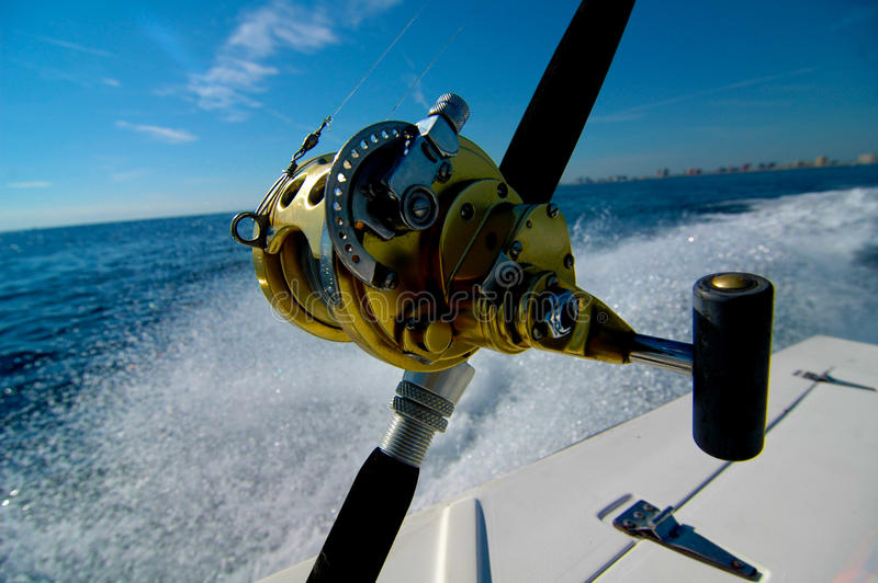 Close up deep sea fishing rod. Deep sea fishing rod in a holder on a boat that is moving very fast. waves are moving from the sides of the boat stock photography