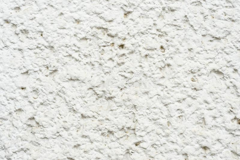 Close-up A deep texture of a white painted porous stone on the facade of the building. Texture background with stone. Wall royalty free stock photography