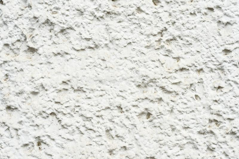 Close-up Deep texture of white-painted porous stone on the facade of the building. Stoned wall background texture.  stock images