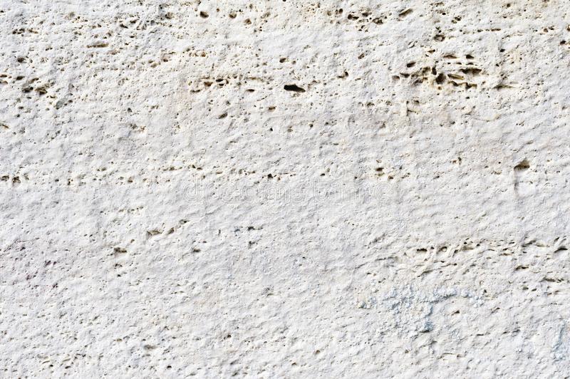 Close-up Deep texture of white-painted porous stone on the facade of the building. Stoned wall background texture.  stock photos