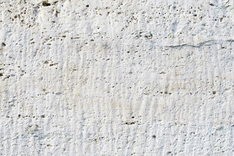 Close-up Deep texture of white-painted porous stone on the facade of the building. Stoned wall background texture.  royalty free stock images