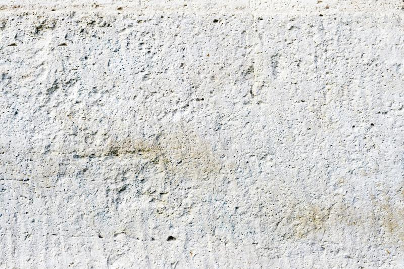 Close-up Deep texture of white-painted porous stone on the facade of the building. Stoned wall background texture.  stock image