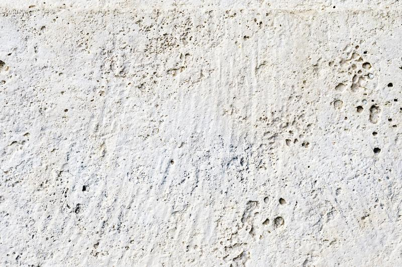 Close-up Deep texture of white-painted porous stone on the facade of the building. Stoned wall background texture.  royalty free stock image