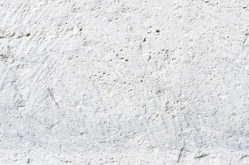 Close-up Deep texture of white-painted porous stone on the facade of the building. Stoned wall background texture.  royalty free stock photography