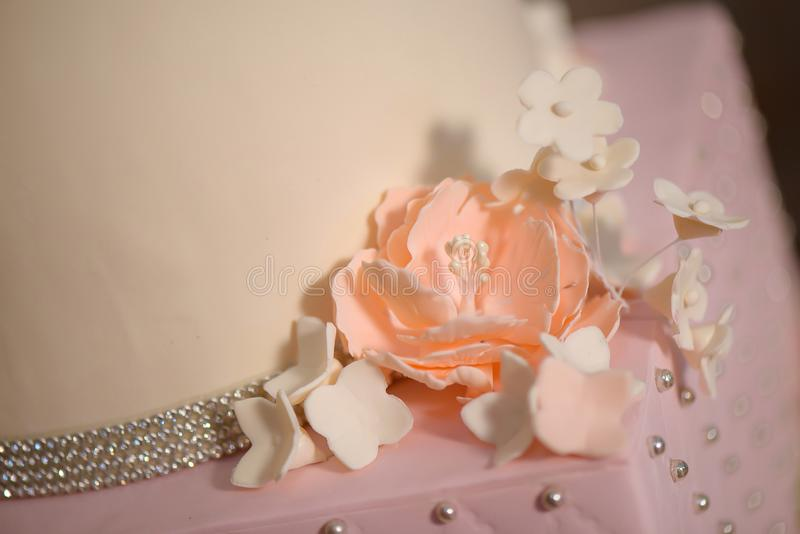 Close up of delicate icing floral decoration on a tiered cake, embellished with velvet pastel pink icing and sugar flowers. Close up of delicate icing floral royalty free stock photos