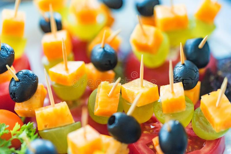 Appetizer of cheese cubes, grapes and tomato. Close up deliccious appetizer with cheese cubes, grapes and tomato on skewers royalty free stock photo