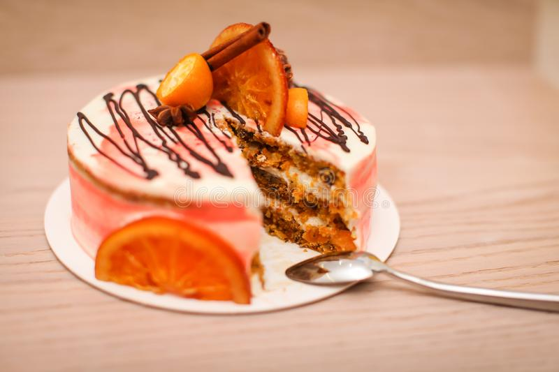 Close up Delicious creamy cake with chocolate, orange slices, cinnamon stick with cutting and spoon stock photography
