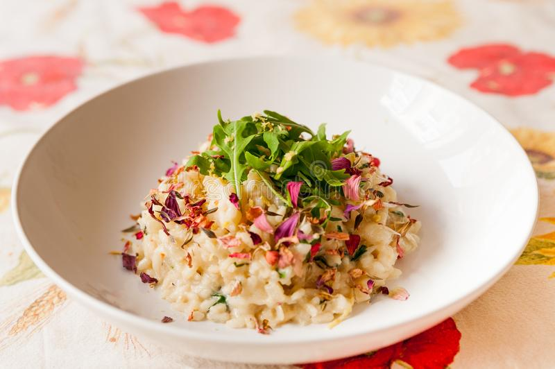 Close up of delicious italian homemade risotto on table cloth with arugula salad lemon and edible flowers and soft natural light royalty free stock photo
